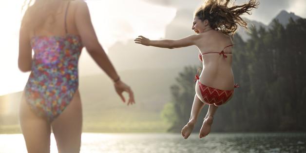2 girls jumping into a lake