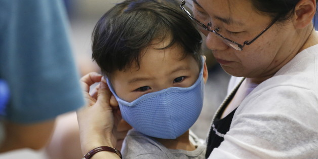 A passenger puts a masks on her son to prevent contracting Middle East Respiratory Syndrome (MERS) at the Incheon International Airport in Incheon, South Korea, June 14, 2015. A South Korean hospital suspended most services on Sunday after being identified as the epicentre of the spread of a deadly respiratory disease that has killed 15 people since being diagnosed in the country nearly four weeks ago.   REUTERS/Kim Hong-Ji
