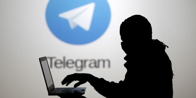 Un homme pose devant un écran montrant le logo de l'application Telegram