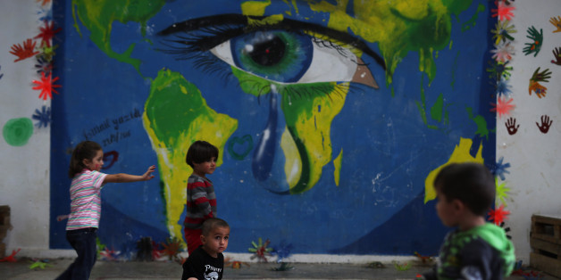 In this photo taken on Tuesday, Sept. 13, 2016, children play in front of a mural at Ritsona refugee camp north of Athens. Most of the people at the camp arrived in Greece in March, crossing to Lesbos and Chios just ahead of an agreement between the EU and Turkey that took effect. Under the deal, anyone arriving on Greek islands from Turkey on or after March 20 would be held on the island and face being returned to Turkey. Balkan countries began restricting crossings of their borders in early 20