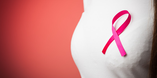 Healthcare, medicine and breast cancer awareness concept - Closeup of pink badge ribbon on woman chest to support breast cancer cause on red