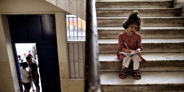 A young girl drawsas she sits in the stairs of an abandoned school used by volunteers for hosting Syrian and Afghan refugees in Athens on July 1, 2016.
