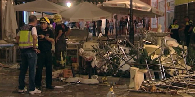 In this grab taken from video, provided by Wikono, emergency services stand outside the cafe La Bohemia, after an explosion, in Malaga, Spain, Saturday, Oct. 1, 2016. More than 70 people have been injured in a gas cylinder explosion near the southern Spanish city of Malaga, according to the local media. (Wikono via AP)