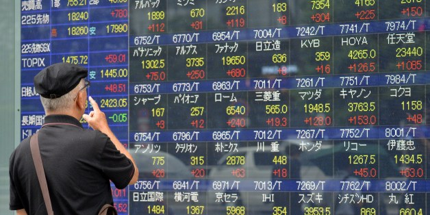 An investor watches a share prices board in Tokyo on September 9, 2015. Japan's share prices rose nearly 5 percent at the Tokyo Stock Exchange, on the back of a jump on Wall Street and on volatile Chinese bourses.  AFP PHOTO / Yoshikazu TSUNO        (Photo credit should read YOSHIKAZU TSUNO/AFP/Getty Images)