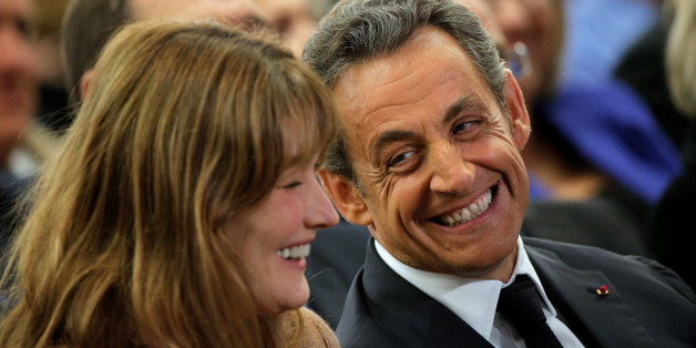 Former French President Nicolas Sarkozy, right, and his wife, Carla Bruni-Sarkozy, smile, during a meeting for the leadership of the conservative UMP party, in Paris, Friday, Nov. 7, 2014. Sarkozy, who drifted into the political wilderness after losing to Hollande in 2012, is seeking the leadership of the conservative UMP party. (AP Photo/Thibault Camus)