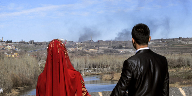 TOPSHOT - A couple hold hands for a wedding photo as they look at smokes rising over the district of Sur in Diyarbakir on February 3, 2016 after clashes between Kurdish rebels and Turkish forces.  Four Turkish soldiers were killed on January 27, 2016 in clashes with Kurdistan Worker's Party (PKK) militants in Diyarbakir in southeast Turkey, as a controversial curfew order was expanded to new areas in the Kurdish-dominated city. / AFP / ILYAS AKENGIN        (Photo credit should read ILYAS AKENGIN/AFP/Getty Images)