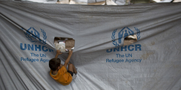 A child play in front of a UNHCR plastic sheet at Ritsona refugee camp, north of Athens, which hosts about 600 refugees and migrants on Thursday, Sept. 8, 2016. The refugee crisis is expected to be a central issue in discussions Friday at a meeting in Athens of leaders from Mediterranean countries in the European Union. (AP Photo/Petros Giannakouris)