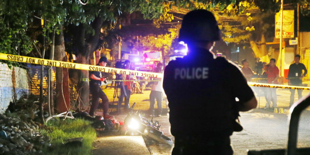 """In this Friday, Sept. 23, 2016 photo, a police SWAT member stands guard as police operatives examine the scene where two bodies lay on a road after being killed in a police drug """"buy-bust"""" operation before dawn in Pasig city, east of Manila, Philippines. Philippine President Rodrigo Duterte said on Thursday he will invite the U.N. chief and European Union officials to investigate his bloody anti-drug crackdown, but only if he can question them in public afterward to prove their human rights concerns are baseless. More than 3,000 suspected drug dealers and users have been killed since July and more than 600,000 others have surrendered for fear of being killed in Duterte's crackdown. Despite growing alarm, Duterte said he won't stop the campaign.(AP Photo/Bullit Marquez, File)"""