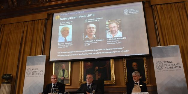 (L-R) The acting chairman of the Nobel Committee for Physics Nils Martensson, the Permanent Secretary of the Royal Swedish Academy of Sciences Goran K Hansson and Thors Hans Hansson, member of the Nobel Committee for Physics sit in front of a screen displaying the winners of the Nobel Prize in Physics (L-R) David J Thouless, F Duncan M Haldane and J Michael Kosterlitz during a press conference to announce the winner of the 2016 Nobel Prize in Physics at the Royal Swedish Academy of Sciences in Stockholm on October 4, 2016. David J. Thouless, F. Duncan M. Haldane and J. Michael Kosterlitz were awarded the 2016 Nobel Physics Prize 'for theoretical discoveries of topological phase transitions and topological phases of matter'. / AFP / JONATHAN NACKSTRAND        (Photo credit should read JONATHAN NACKSTRAND/AFP/Getty Images)