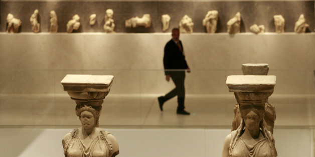 A security guard walks past Caryatid statues during the official opening ceremony of the New Acropolis Museum in Athens, June 20, 2009. Greece opened the gates of the long-awaited Acropolis Museum on Saturday, hoping the modern glass and concrete building will help bring back the Classical Parthenon sculptures from Britain.      REUTERS/John Kolesidis (GREECE POLITICS SOCIETY)