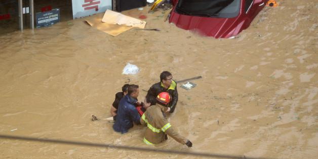 태풍 차바의 영향으로 울산에 300㎜가 넘는 폭우가 쏟아지면서 곳곳이 침수됐다. 목까지 물에 잠기는 중구 우정동에서 소방관들이 고립된 시민을 구조하고 있다.