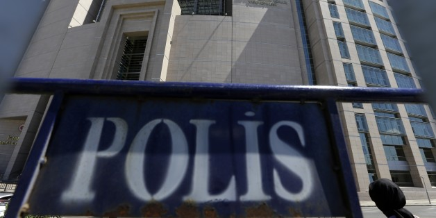A woman enters a courthouse as a police fence is on display outside the building in Istanbul, on Monday, Aug. 15, 2016. Turkey's state-run news agency says police teams are conducting operations at three Istanbul courthouses as part of an investigation into the July 15 abortive coup. (AP Photo/Thanassis Stavrakis)
