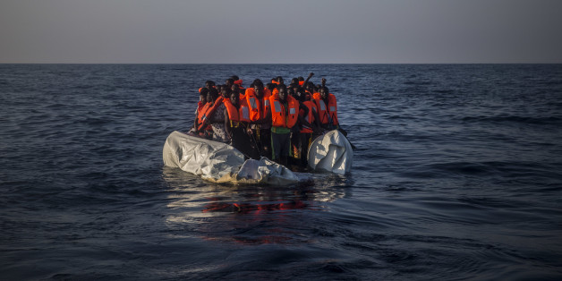 In this photo taken on Saturday Sept. 10, 2016, African refugees and migrants wait aboard a partially punctured rubber boat to be assisted, during a rescue operation on the Mediterranean Sea, about 13 miles North of Sabratha, Libya. (AP Photo/Santi Palacios)