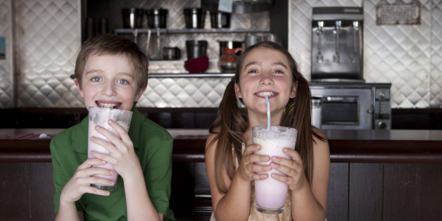 Boy and girl enjoying milkshakes