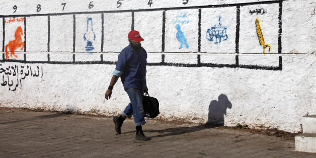 A man walks past a wall marked by the numbers of districts where civilians should go to vote, in Rabat November 18, 2011. Morocco will hold parliamentary elections on November 25. REUTERS/Stringer (MOROCCO - Tags: ELECTIONS POLITICS)