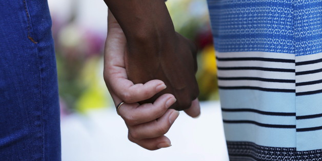 Mourners hold hands outside the Emanuel African Methodist Episcopal Church in Charleston, South Carolina, June 18, 2015 a day after a mass shooting left nine dead during a bible study at the church. Dylann Roof, a 21-year-old white man, was arrested on Thursday on suspicion of having fatally shot nine people at the historic African-American church in South Carolina. The U.S. Department of Justice is investigating Wednesday's attack as a hate crime, motivated by racism or other prejudice. REUTERS/Brian Snyder