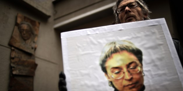 A man holds a portrait of slain Russian journalist Anna Politkovskaya during a rally marking the 8th anniversary of her death in Moscow on October 7, 2014. Politkovskaya was gunned down in Moscow in 2006. AFP PHOTO/KIRILL KUDRYAVTSEV        (Photo credit should read KIRILL KUDRYAVTSEV/AFP/Getty Images)