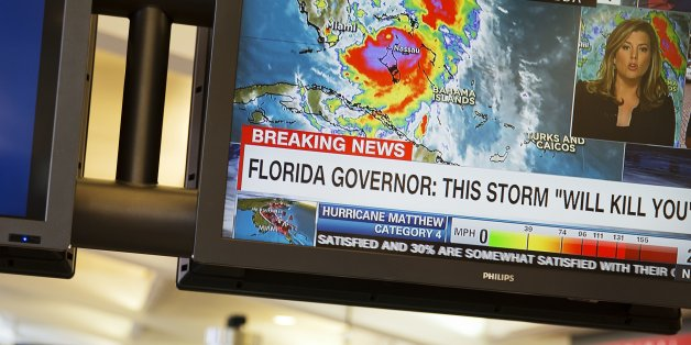 A monitor shows a television news report on Hurricane Matthew as travelers collect their baggage after arriving at Hartsfield-Jackson Atlanta International Airport in Atlanta, Thursday, Oct. 6, 2016. Airlines canceled hundreds of flights for Thursday and again Friday as Hurricane Matthew pelted the Florida coast with high winds and heavy rain. (AP Photo/David Goldman)