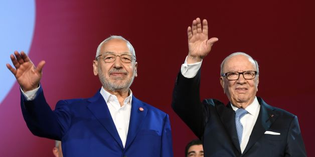 Tunisian president Beji Caid Essebsi (R) and Islamist Ennahdha Party leader Rached Ghannouchi (L) wave to the crowd on May 20, 2016 at the opening of Ennahdha's three-day congress in Tunis. Thousands of people attended the opening ceremony of the congress -- the first since 2012 -- held at a sports complex in Rades, south of the capital Tunis, amid heavy police security. / AFP / FETHI BELAID        (Photo credit should read FETHI BELAID/AFP/Getty Images)