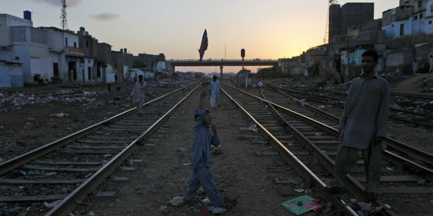 A Pakistani boy plays with a kite between railway tracks in Karachi, Pakistan, Tuesday, Oct. 29, 2013.  (AP Photo/Shakil Adil)