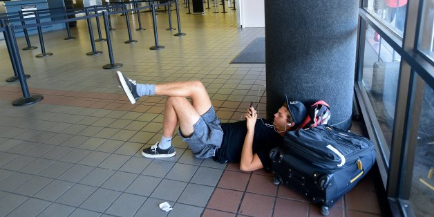 Traveller Santiago Aldrete, who arrived from Bali and is awaiting his flight to Mexico City, gets comfortable on the ground while charging his phone at Los Angeles International Airport on July 1, 2016 where a record 1.207 million people are expected to pass through during their travels over the Fourth of July weekend. LAX officials said the number of travelers anticipated to use the airport is up 9.7 percent from last year's record 1.1 million people over the holiday travel period, which runs f