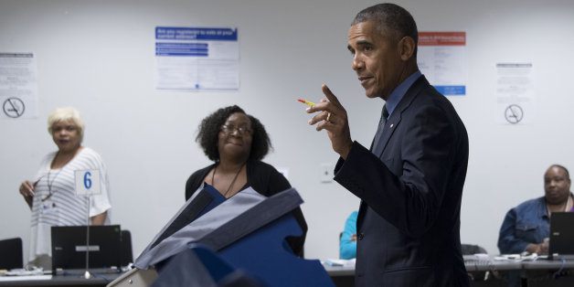 Poll workers look on as US President Barack Obama (C) gestures towards the press as he votes early at the Cook County Office Building in Chicago, Illinois, October 7, 2016.Obama cast an early ballot on Friday, highlighting a Democratic drive to get voters to the polls even before November 8. During an unannounced visit, Obama stood before a voting machine at the Chicago Board of Elections office, punched in his choice and smirked when asked who he had voted for. / AFP / JIM WATSON        (Photo