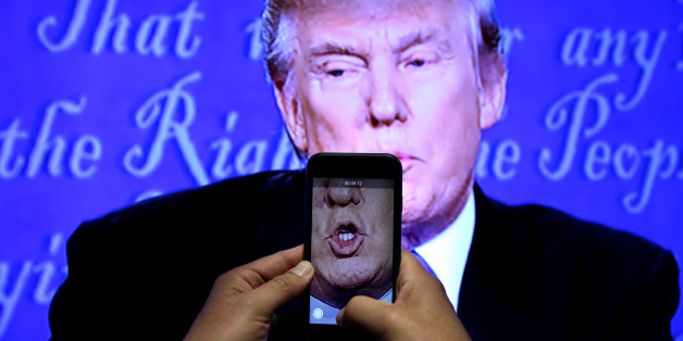 A journalist records a video from screen as Republican U.S. presidential nominee Donald Trump speaks during the first presidential debate with U.S. Democratic presidential candidate Hillary Clinton at Hofstra University in Hempstead, New York, U.S. on September 26, 2016. REUTERS/Carlos Barria/File Photo