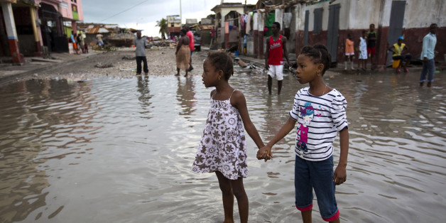 Girls hold hands as they help each other wade through a flooded street after the passing of Hurricane Matthew in Les Cayes, Haiti, Thursday, Oct. 6, 2016. Authorities and aid workers fear the storm is the country's biggest disaster in years (AP Photo/Dieu Nalio Chery)