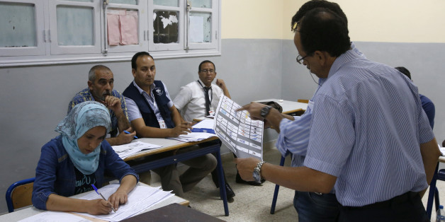 The president of a polling station shows a ballot as officials and political party's representatives count the ballots as from left to right observers Moroccan Omar Eloufir from Moroccan League for Citizenship and Law Man,  second left, Tunisian Mouldi Ayari from Election Network in the Arab Region and Moroccan Ahmed Bazzi  from National Observatory of voter rights second right , back, looks on in the polling station in Rabat, Morocco, Friday, Oct. 7, 2016. Amid worries about jobs and extremism,