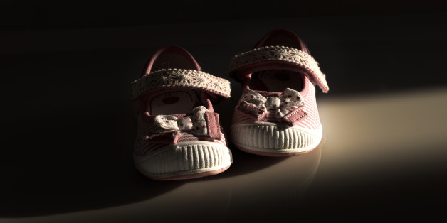 Conceptual image of violence to kids represented with a pair of baby shoes on a dark background