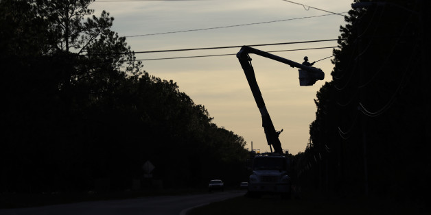 Crews remove limbs from power lines after winds from Hurricane Matthews hit the area, Saturday, Oct. 8, 2016, in Flagler Beach, Fla. Thousands of residents and businesses are with out power. (AP Photo/Eric Gay)