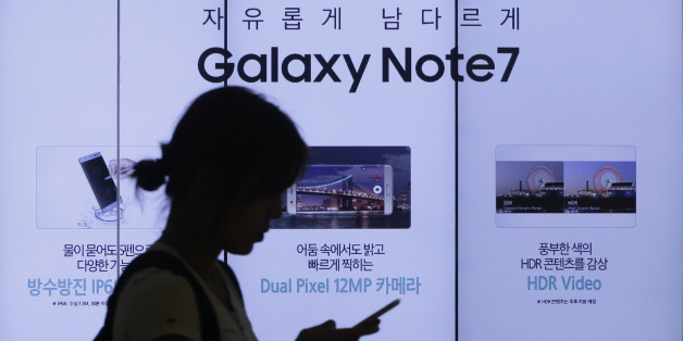 FILE - In this Friday, Sept. 2, 2016, file photo, a woman walks by an advertisement of the Samsung Electronics Galaxy Note 7 smartphone at the company's showroom in Seoul, South Korea. The Federal Aviation Administration said Thursday night, Sept. 8, 2016, that because of recent fire reports involving the Galaxy Note 7 smartphone, passengers shouldn't use or charge one or stow one in checked baggage. The three biggest U.S. airlines: American, Delta and United, said Friday that they were stu