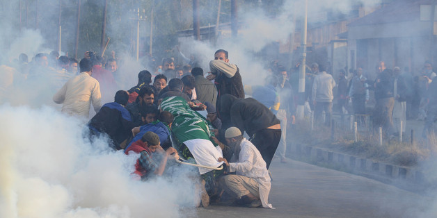 INDIA - 2016/10/08: People try to protect the dead body of 12 year old boy Junaid Ahmad after Indian police resorted to heavy teargas shelling in Srinagar the summer capital of Indian controlled Kashmir on October 08, 2016. Indian police resorted to intense teargas shelling on people in Eidgah area of Srinagar who were heading to bury the dead body of Ahmad. Junaid was shot dead after Indian police fired pellets in his head and chest without any provocation, local residents said. (Photo by Faisal Khan/Pacific Press/LightRocket via Getty Images)