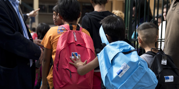 Refugee children enter a primary school in  Athens during the first day of lessons under the new refugee schooling program, on Monday, Oct. 10, 2016. More than 60,000 refugees are stranded in Greece due to European border closure. (AP Photo/Petros Giannakouris)