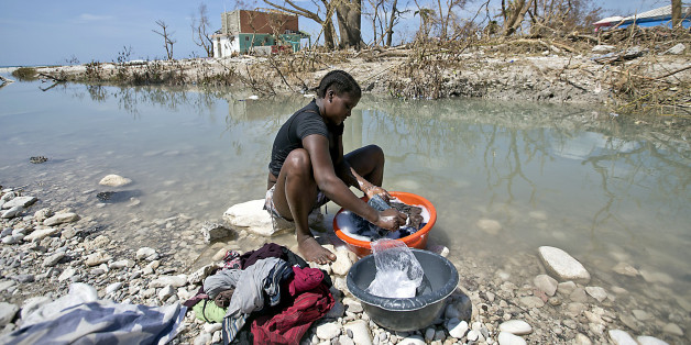 Natalie Joseph cleans clothes in a river cutting through Roche a Bateau, Haiti on Sunday, Oct. 9, 2016.   (Patrick Farrell/Miami Herald/TNS via Getty Images)
