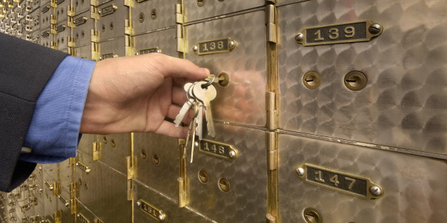 Man's hand holding key to safety deposit box, close-up