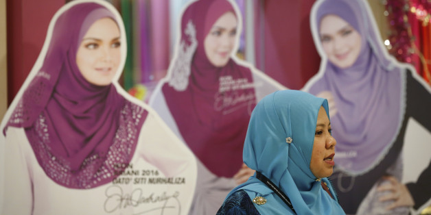 A Muslim woman walks by cutouts displayed during the World Muslim Women Summit and Exhibition in Kuala Lumpur, Malaysia, Friday, Sept. 23, 2016. The summit is expected to serve as a catalyst for other Muslim countries to continuously uphold and strengthen the roles of Muslim women in accordance with the principles of Quran. (AP Photo/Vincent Thian)