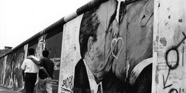 A gay couple strolling past graffiti on the Berlin Wall depicting German leaders Leonid Brezhnev and Erich Honecker sharing a kiss, August 1993. (Photo by Steve Eason/Hulton Archive/Getty Images)