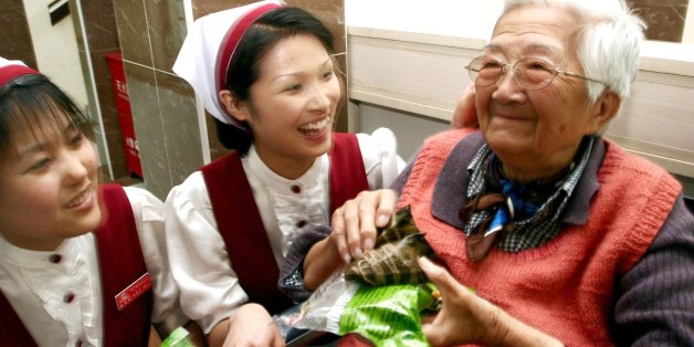 NANJING, CHINA - MAY 31, 2006: (CHINA OUT)   Beijing Weiduomei Foods Co. Ltd. present zongzi to an eldery member of the Welfare Institution on May 31, 2006 in Nanjing, China . May 31 is the Chinese traditional Dragon boat festival which is one of three major Chinese holidays, along with the Spring and Moon Festivals. Of the three, it is possibly the oldest, dating back to the Warring States Period in 227 B.C. The festival commemorates Qu Yuan, a minister in the service of the Chu Emperor. Despairing over corruption at court, Qu threw himself into a river. Townspeople jumped into their boats and tried in vain to save him. Over the years, the story of Qu's demise transformed into the traditions of racing dragon boats and eating zongzi,  a kind of rice wrapped in bamboo leaves.  (Photo by VCG via Getty Images)