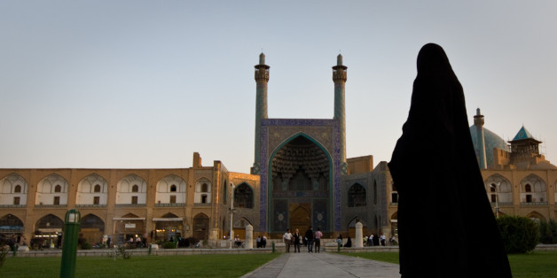Iran woman walking in towards Shah mosque located in Naghsh i Jahan square in center of Isfahan, Iran.