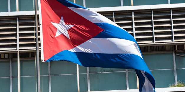 HAVANA CITY, HAVANA, CUBA - 2015/09/19: Cuban flag in pole with building design in the background.The flag of Cuba consists of five blue and white alternating stripes, and a red equilateral triangle at the hoist with a white five-pointed star. (Photo by Roberto Machado Noa/LightRocket via Getty Images)