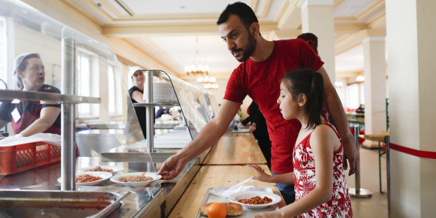 """Syrian refugee Moustafa Shikh Habib and his daughter Noor take some food in the refugee shelter where they live on the first day of the Islamic holiday of Eid al-Fitr the end of the fasting month of Ramadan, in Berlin, Germany, Tuesday, July 5, 2016. """"It's difficult to be away from all the family, from my brothers, on this special day,"""" the 36-year-old Kurd Moustafa said at his new home in Berlin, two little cramped rooms he shares with his family. (AP Photo/Markus Schreiber)"""