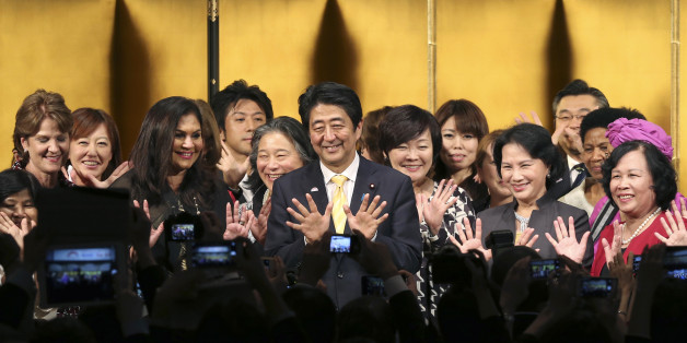 Japanese Prime Minister Shinzo Abe, center, poses for a photo with participants during a reception of WAW!, or the World Assembly for Women, in Tokyo, Friday, Aug. 28, 2015. More than 100 people from about 40 countries participated in the open forum for women. Japanese lawmakers approved a law Friday requiring large employers to set and publicize targets for hiring or promoting women as managers. The law approved by a vote of 230-1 in the House of Councillors is intended to promote greater gende