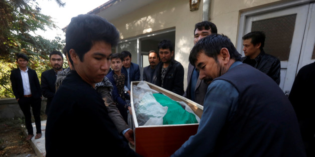 Afghan men carry the dead body of a civilian at a hospital after gunmen attacked a shrine in Kabul, Afghanistan October 12, 2016. REUTERS/Omar Sobhani