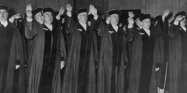 (GERMANY OUT) GERMANY: JUDGES, 1936. /nCeremony in criminal court at Berlin with judges displaying their loyalty to the Nazi Party (note party insignia on their robes), 1 October 1936. (Photo by ullstein bild/ullstein bild via Getty Images)