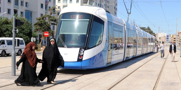 Women cross in front of a new tramcar on May 8, 2011 in Algiers. After a two-year delay, the new tramway service opened, starting with a 7.2 km section running between Bordj El Kiffan and Bab-Ezzouar, serving residents in the densely populated eastern part of the city. AFP PHOTO / FAROUK BATICHE (Photo credit should read FAROUK BATICHE/AFP/Getty Images)