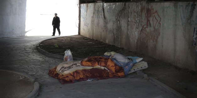 "A homeless man sleeps under a bridge as an elderly woman walks past in Athens, Thursday March 19, 2015. Parliament on Wednesday approve an anti-poverty bill, that would provide assistance worth some 200 million euros ($212.7 million) to mostly jobless households considered to be in ""extreme poverty."" (AP Photo/Petros Giannakouris)"