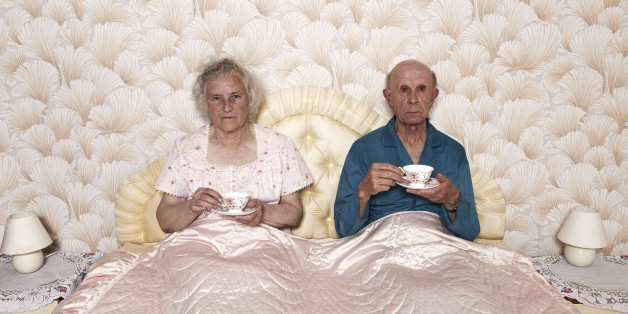 senior married pensioners aged two people dated retro sharing patterned chintz Caucasian wallpaper bedtime routine repetitive dotage long suffering husband wife male female man woman retired retirement resignation