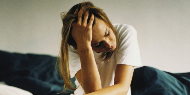 Young woman sitting on edge of bed, holding head in hand