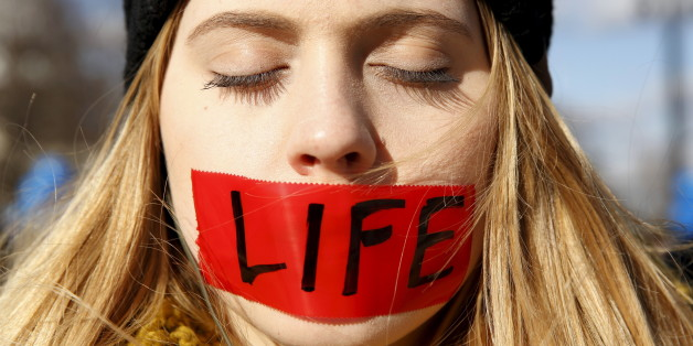 "A protester with her mouth taped over with the word ""life"" stands in front of the U.S. Supreme Court on the morning the court takes up a major abortion case focusing on whether a Texas law that imposes strict regulations on abortion doctors and clinic buildings interferes with the constitutional right of a woman to end her pregnancy, in Washington March 2, 2016. REUTERS/Kevin Lamarque       TPX IMAGES OF THE DAY"